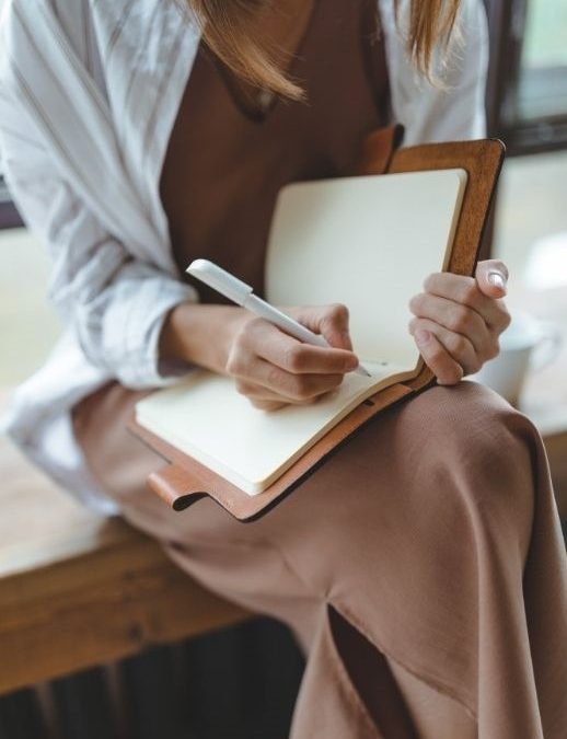 Girl writing in journal - How to set goals you will achieve